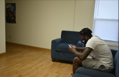 Photo of a student sitting alone in university residence. Photo by Robert Purchase II.